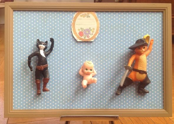 Cadre de naissance en materiaux recycles . Dimensions : 32X22 cm 2 figurines Chat Botte et Catwoman entourent un petit bebe garçon .