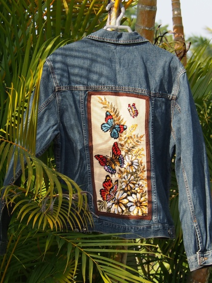Blouson en jean vintage taille M , décoré avec un canevas fond écru motif papillon . Cerné avec un galon dentelle marron .