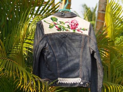 Blouson en jean vintage taille S , revisité avec un canevas écru motif roses au niveau du haut du dos . Un galon dentelle au bas du blouson .