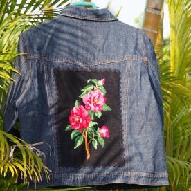 Canevas bouquet de roses sur fond noir bordé d'un galon zig zag noir . Le blouson est de taille L .